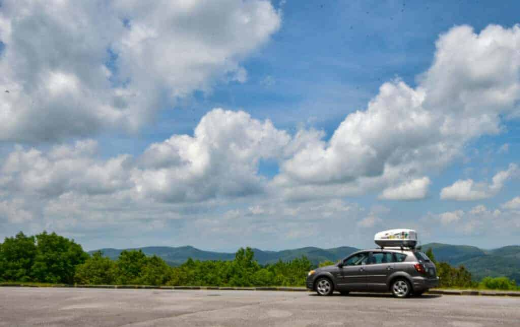 A small grey car parked at an overlook on the Blue Ridge Parkway in Virginia.