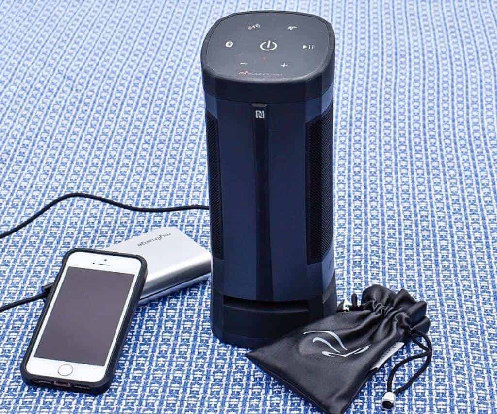The Soundcast VG3 outdoor speaker next to an iPhone and a portable power bank.