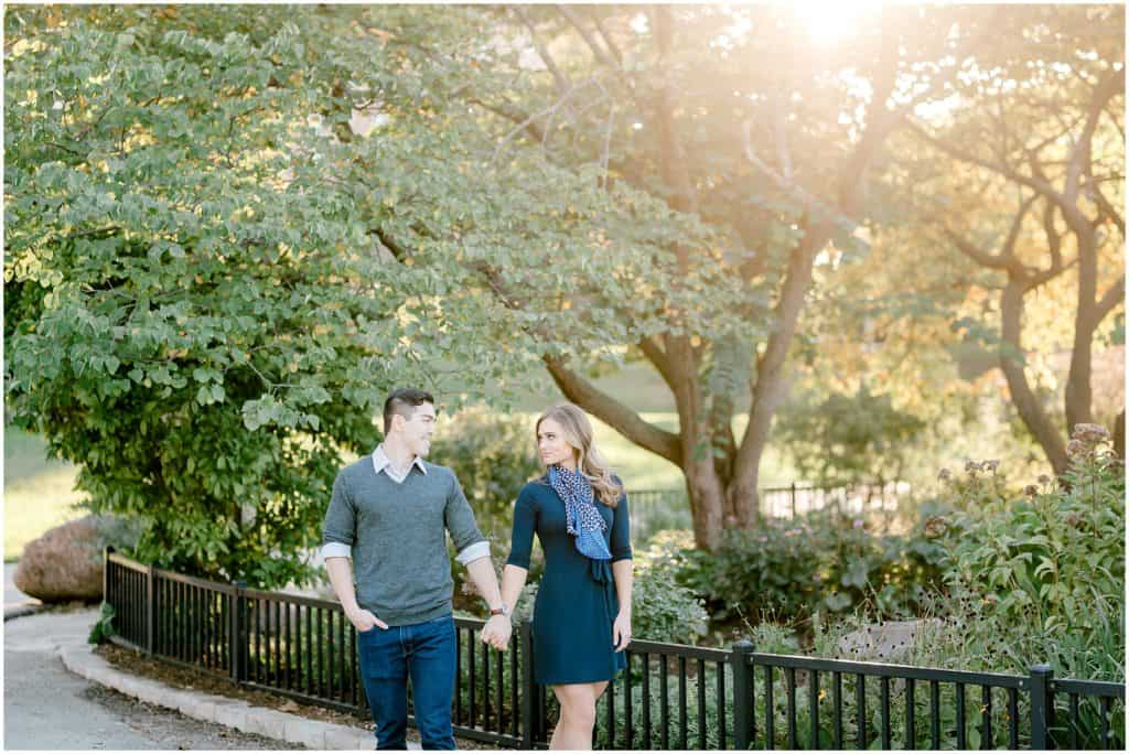 couple walking in the Chicago Lincoln Park during  golden hour engagement session