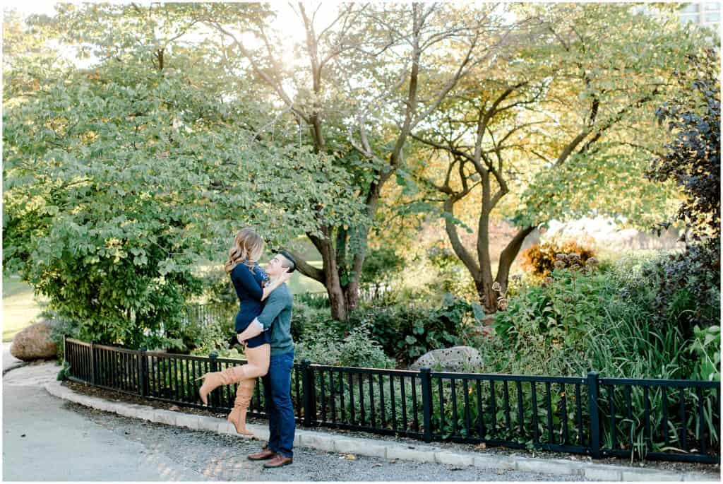 sunset engagement session in Chicago Lincoln park zoo, guy is lifting girl, they are looking at each other with love