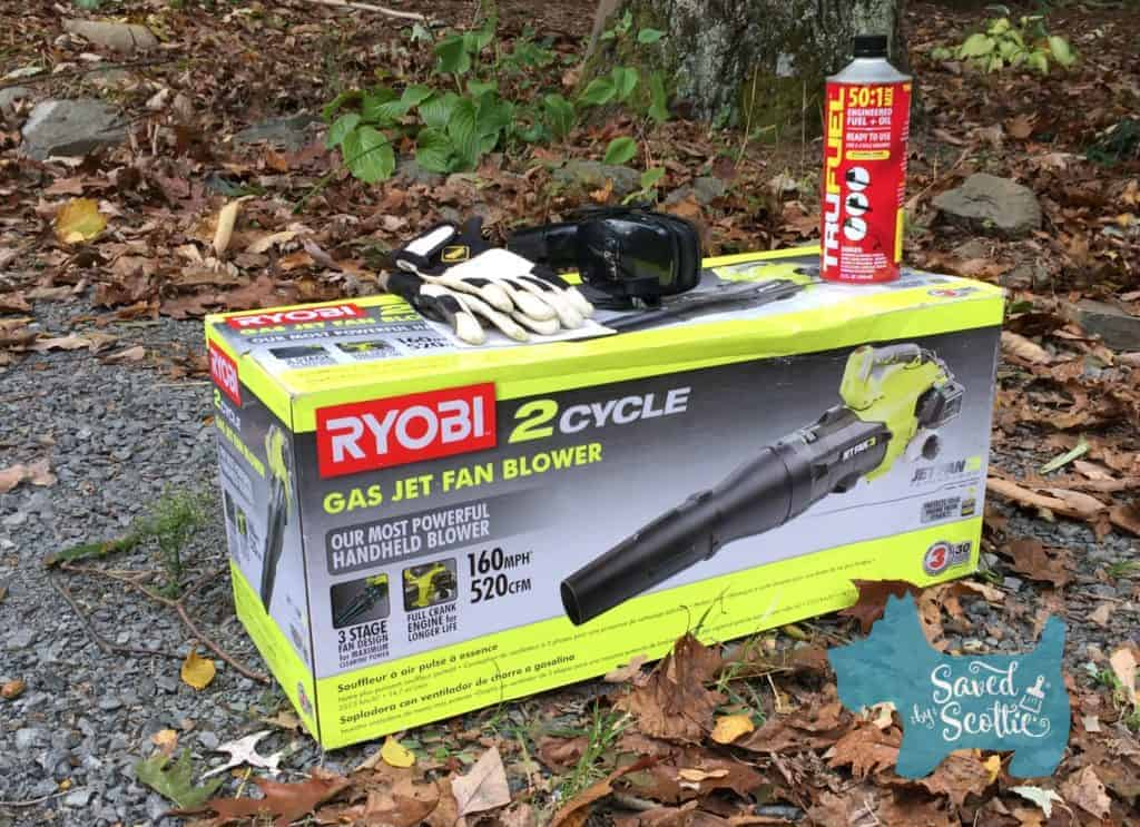 Photo of the Ryobi 2 Cycle Gas Jet Fan Blower in the box, with the fuel on top, as well as some safety supplies (gloves, ear protection).