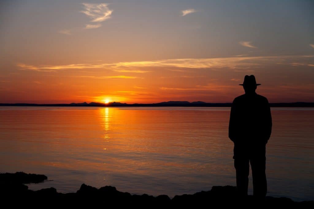 Old man with a hat on watching the sunset in Galway bay in Ireland.