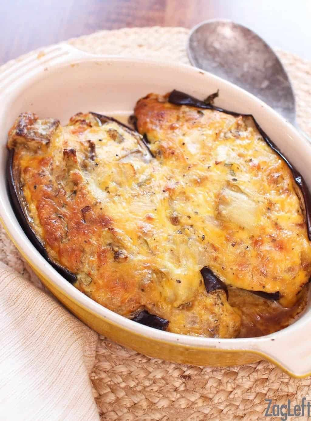 Two halves of twice baked eggplant in a cooking dish
