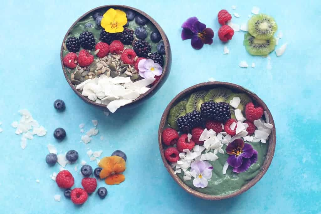 Two green smoothie bowls made with spirulina and topped with fresh fruit