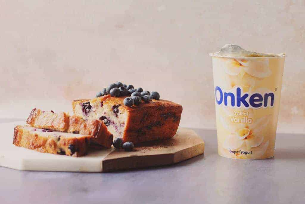 Bluberry banana bread cut into slices and topped with fresh blueberries beside a pot of Onken yoghurt