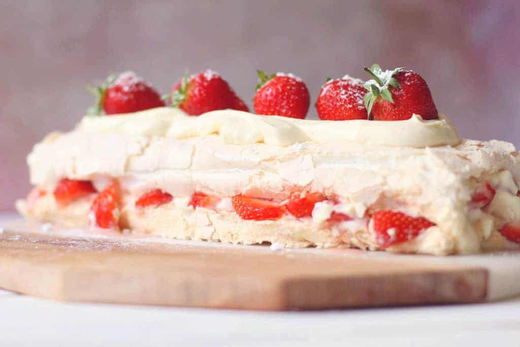 An eton mess roulade topped with whole strawberries