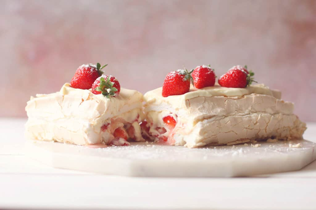An Eton Mess Roulade cut in half with strawberries on top and a cream and yoghurt filling