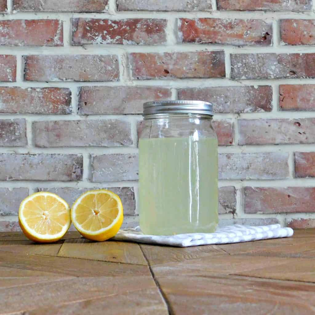 homemade bleach in mason jar beside cut lemon on wood table
