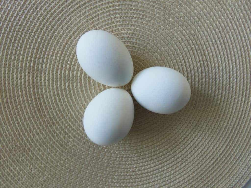 three eggs pointing together on a placemat