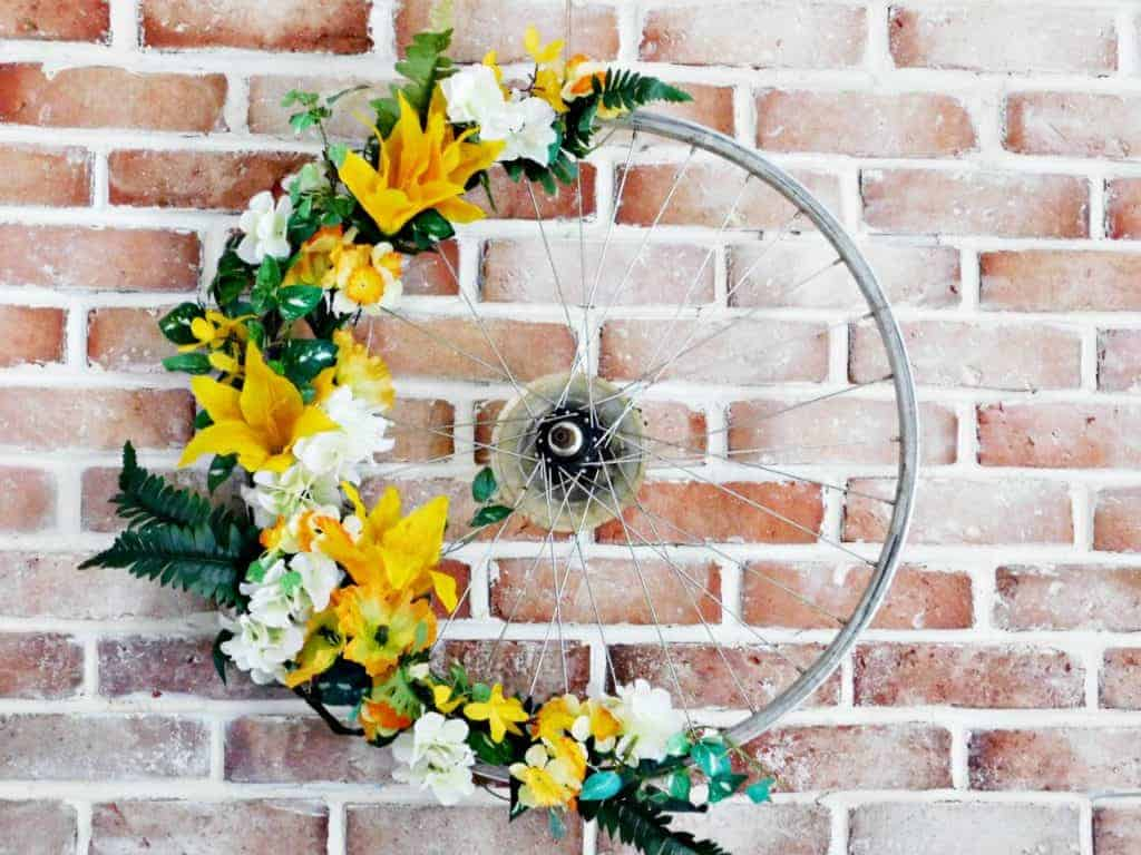 Bicycle Wheel Wreath rim with yellow flowers on brick wall