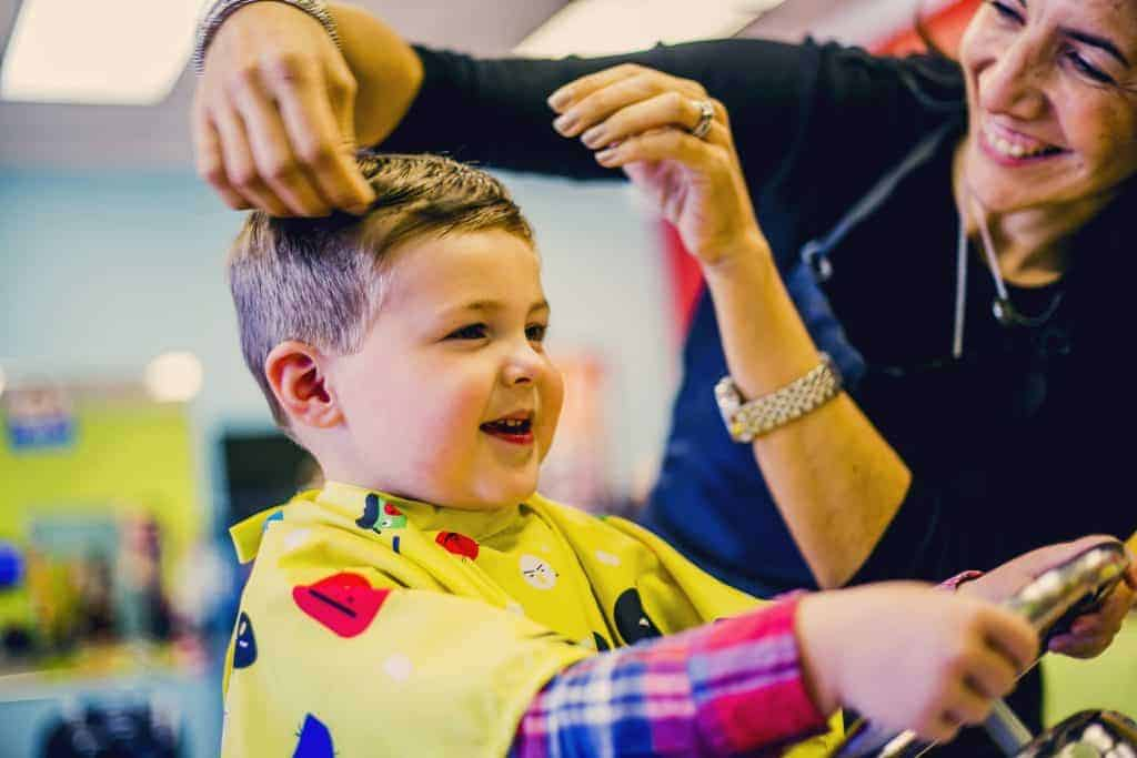 small boy gets haircut at Pigtails & Crewcuts kid's haircut franchise