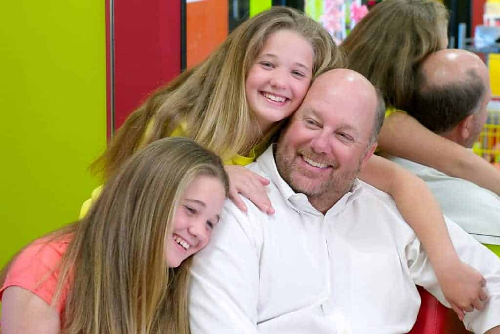 Wade Brannon in a Pigtails & Crewcuts salon with his daughters