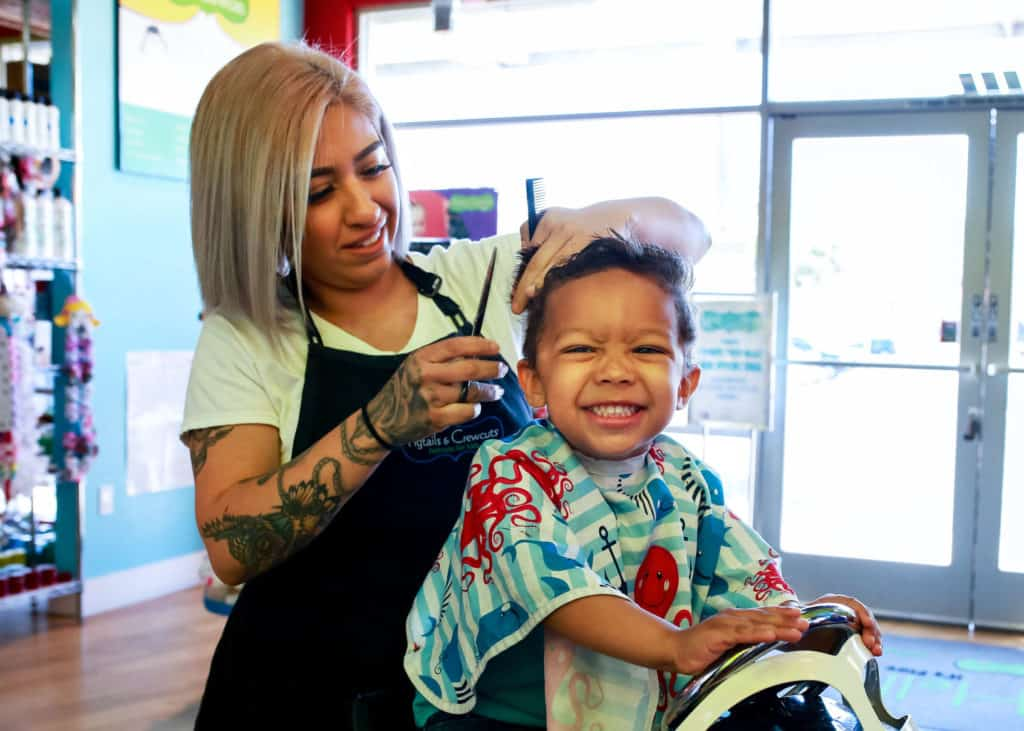 happy boy getting haircut at pigtails & crewcuts