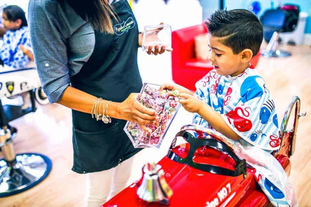 little boy choosing a lollipop after getting his hair cut at Pigtails & Crewcuts kids hair salon