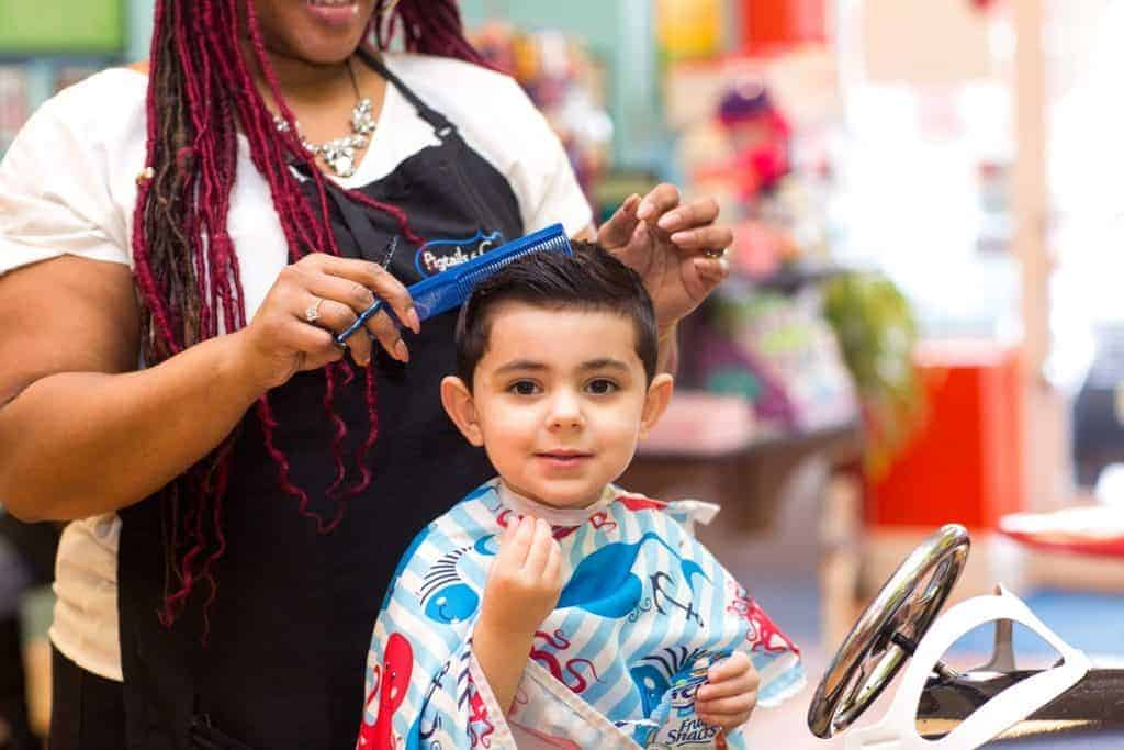boy getting his hair cut at pigtails & crewcuts franchise