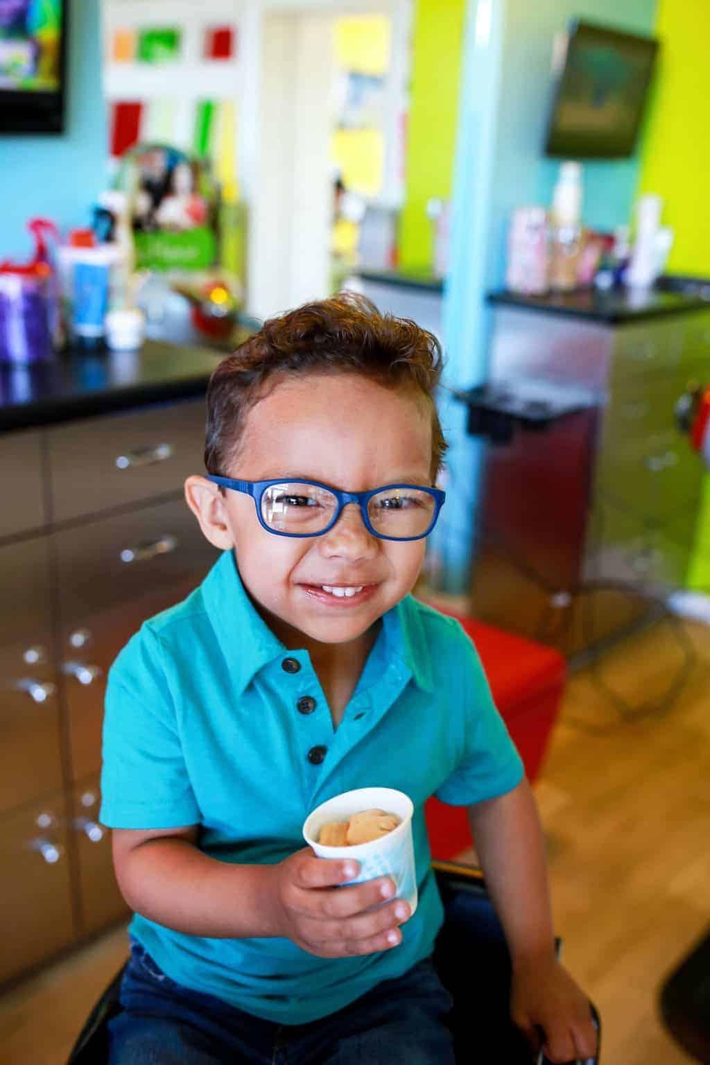 smiling boy wearing glasses sitting in pigtails & crewcuts franchise