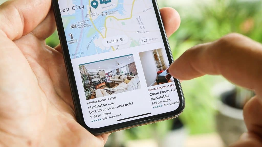 NEW YORK CITY, NY – December 1, 2019: Woman trying to book home apartment room in New York City using Airbnb app