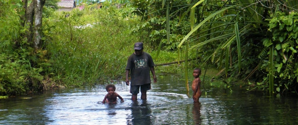 Papuan man with two kids in a river in West Papua while exploring Sorong and surroundings