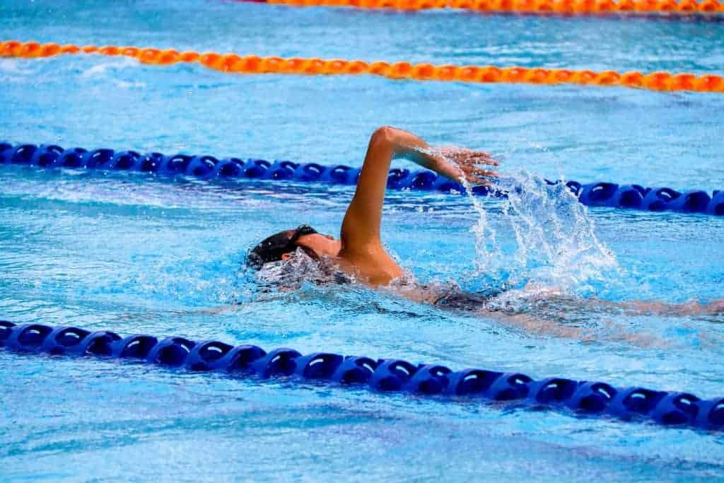 man swimming in olympic swimming pool