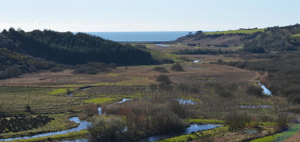 The spectacular seaward view from Dunhill Castle over the Anne Valley showing the River Anne meandering towards the sea - The Irish Place