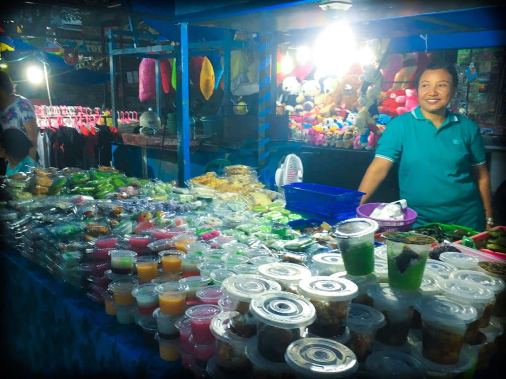 A food vendor at a Bali night market in Gianyar, Indonesia selling jellies in plastic cups and sweet treats in plastic containers