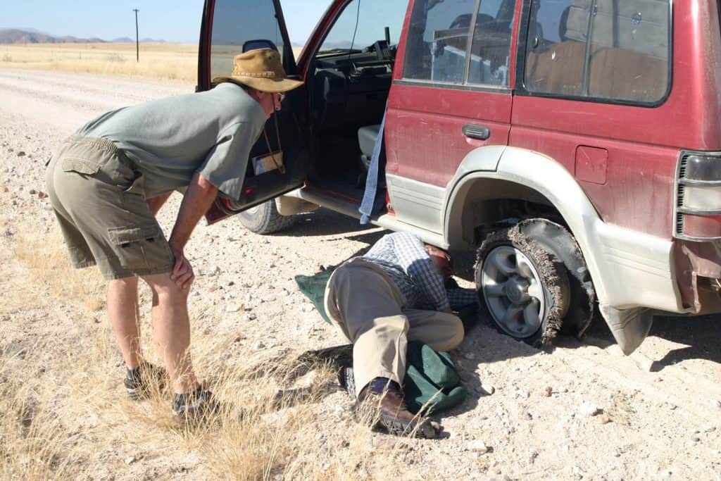 Passenger looking at damage on Pajero with burst tyre, next to gravel road.