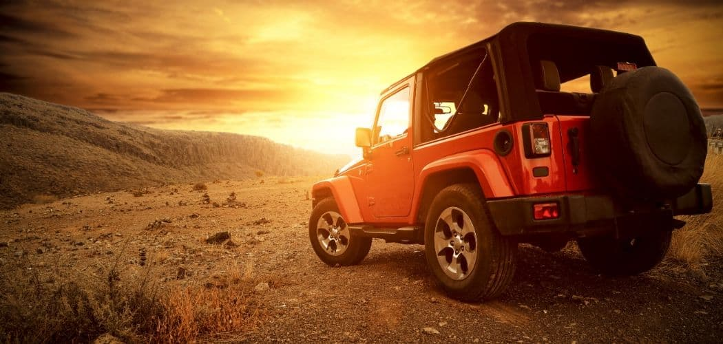 jeep color red with soft top and sunlight