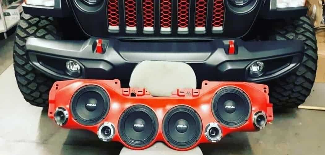 speakers in sound bar in front of red jeep wrangler