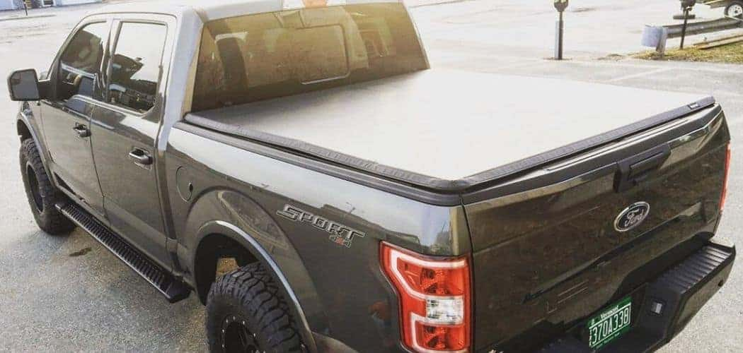 ford f150 with tonneau and bed cover along road