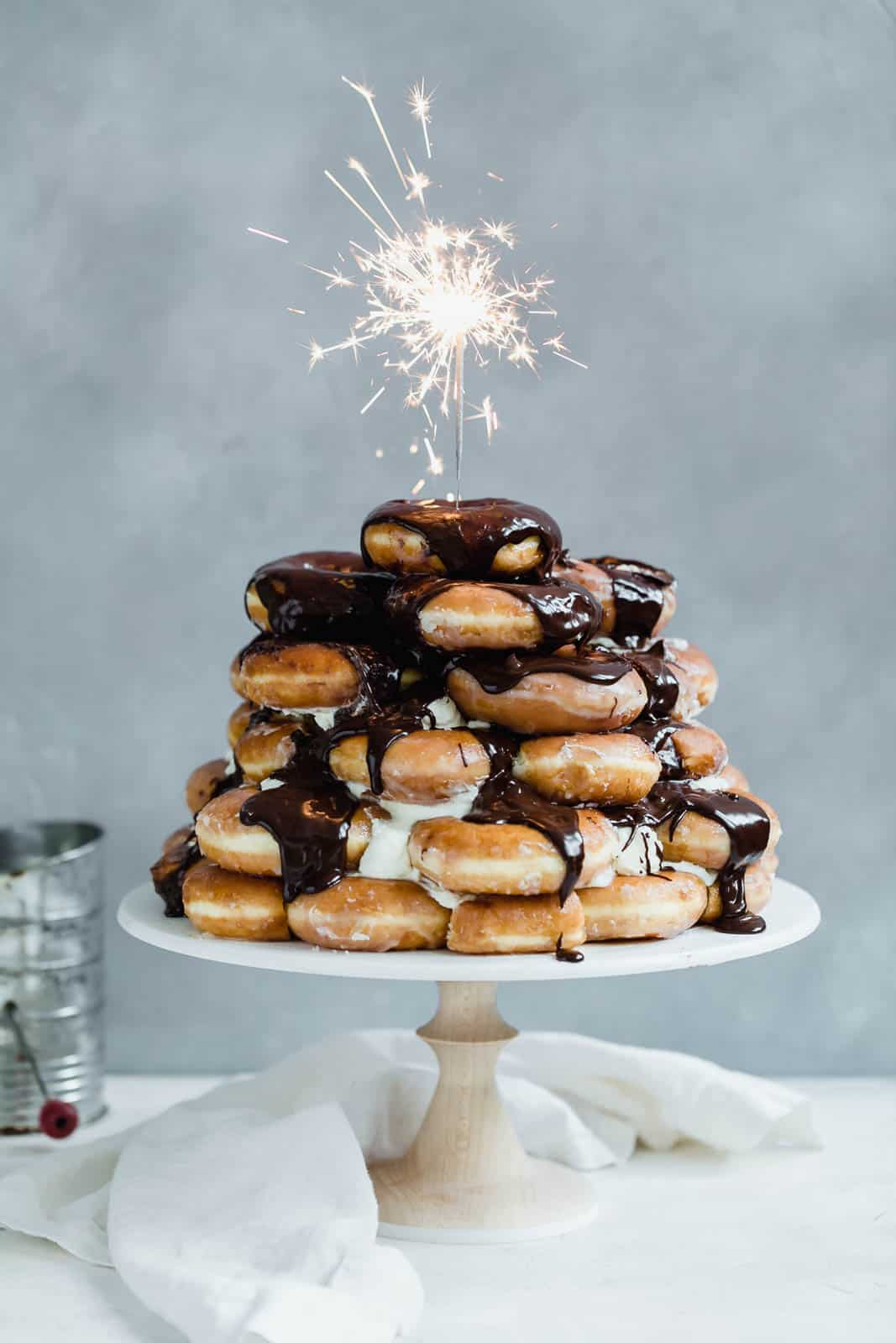 Towering Krispy Kreme donut cake smothered in chocolate frosting