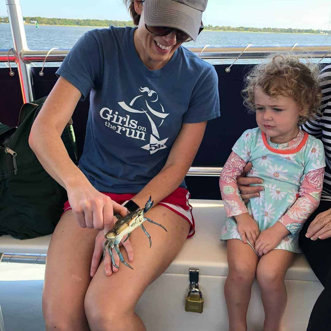 Woman holds live crab to show young girl. Nature boat tours Charleston