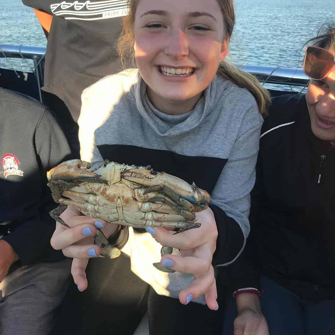 Young girl holding a live crab. Nature boat tours Charleston