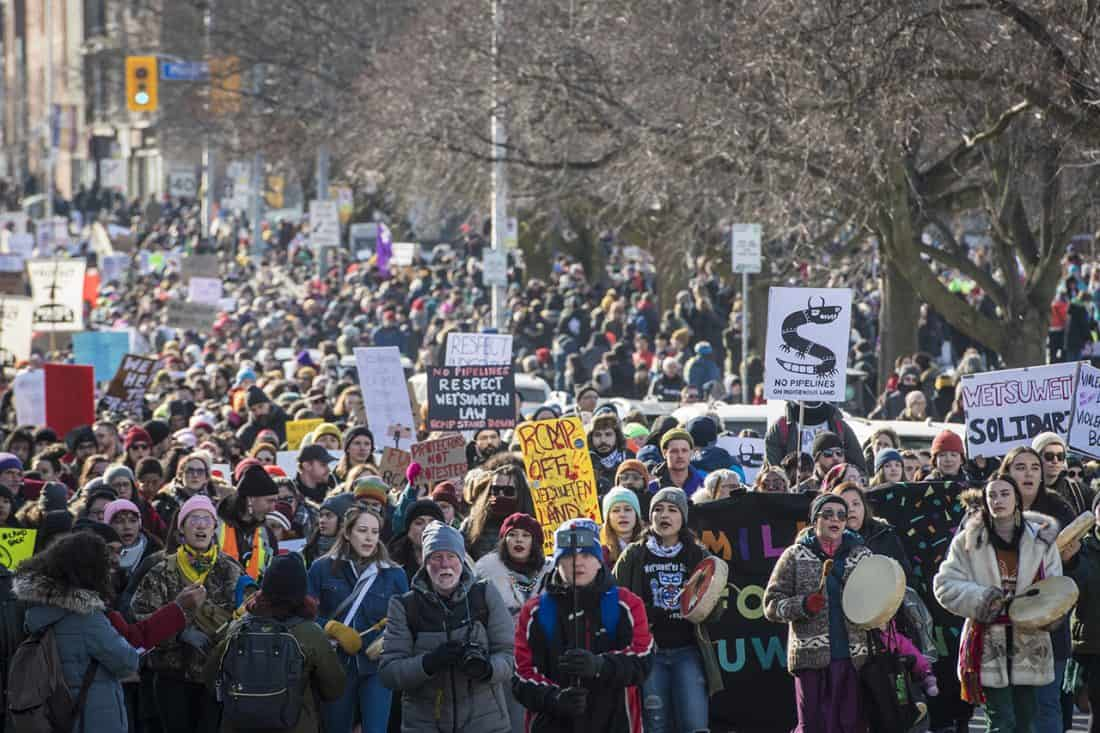 A large crowd bearing signs and drums swarm down an avenue.