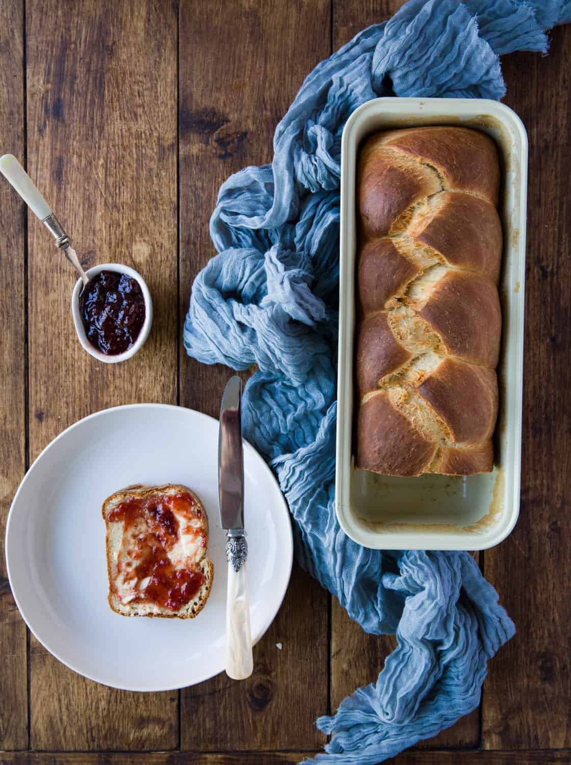 A loaf od brioche bread with a slice cut from it covered with butter and jam