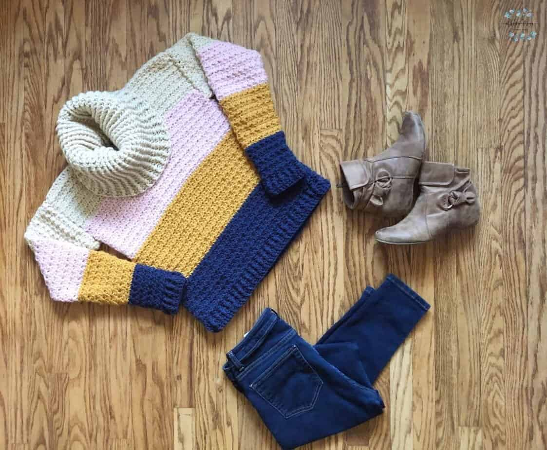 picture of flat lay women's cowl neck sweater with jeans and boots