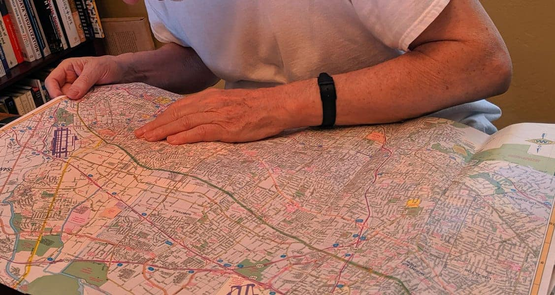 Man reading a street map at a table.