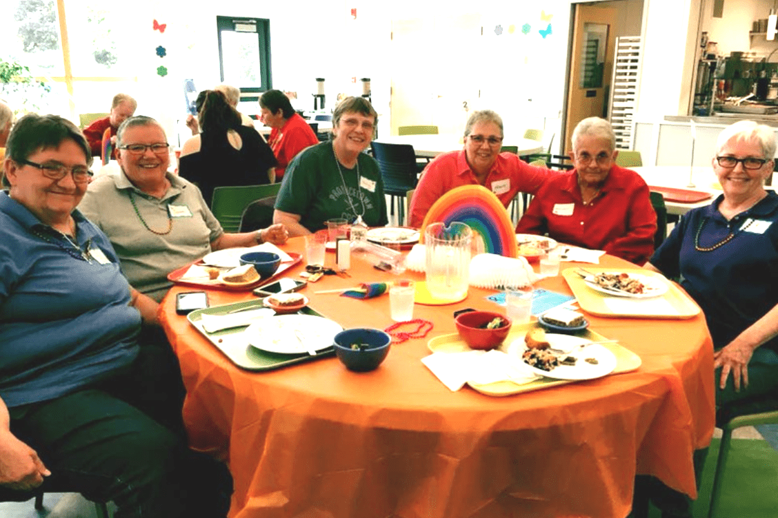 group of people smiling sitting around an orange table with plates of food on it and a rainbow decoration