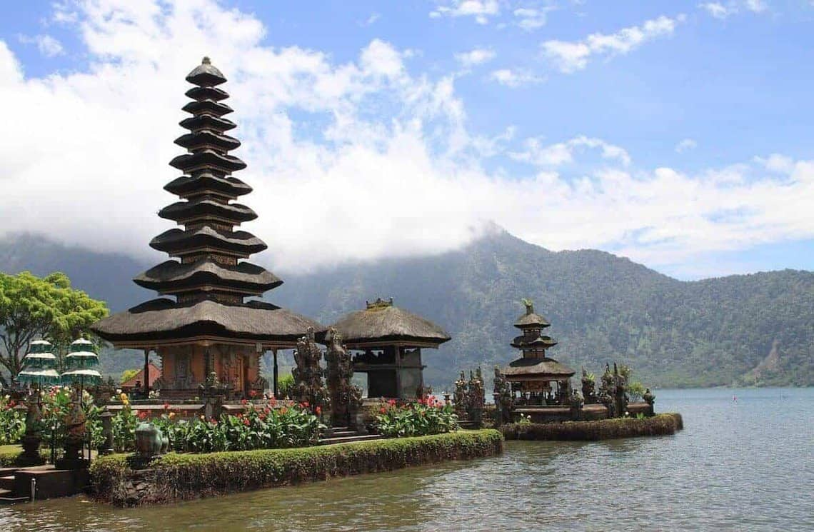 Tall brown wooden pagoda rising towards a blue sky with white clouds next to a lake - cover shot for the best things to do in Bali and guide to the best places to visit in Bali