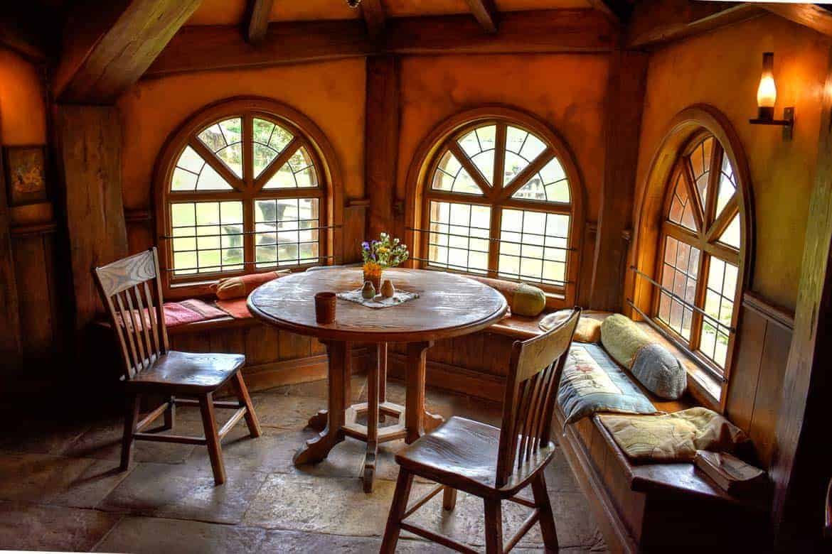 The Green Dragon Inn warm interior with chairs by the round windows in Hobbiton Movie Set