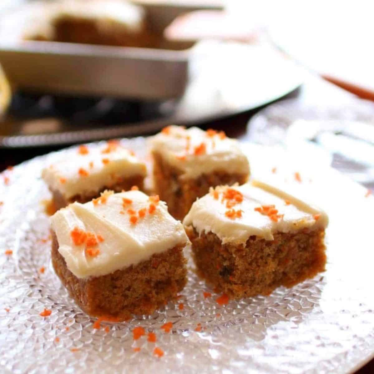 four squares of carrot cake on a clear plate next to a partially cut cake.