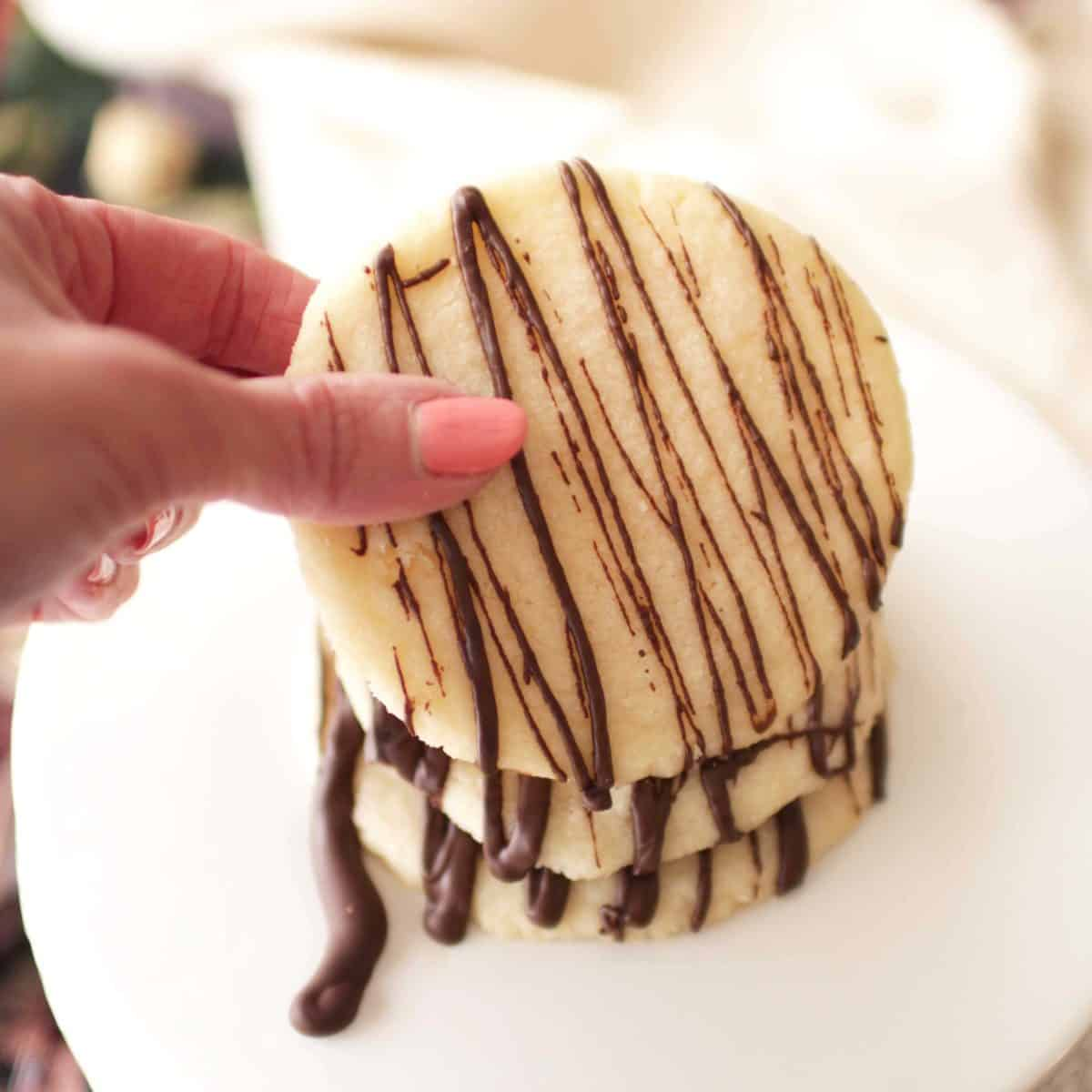 fingers holding up a shortbread cookie with a chocolate drizzle.