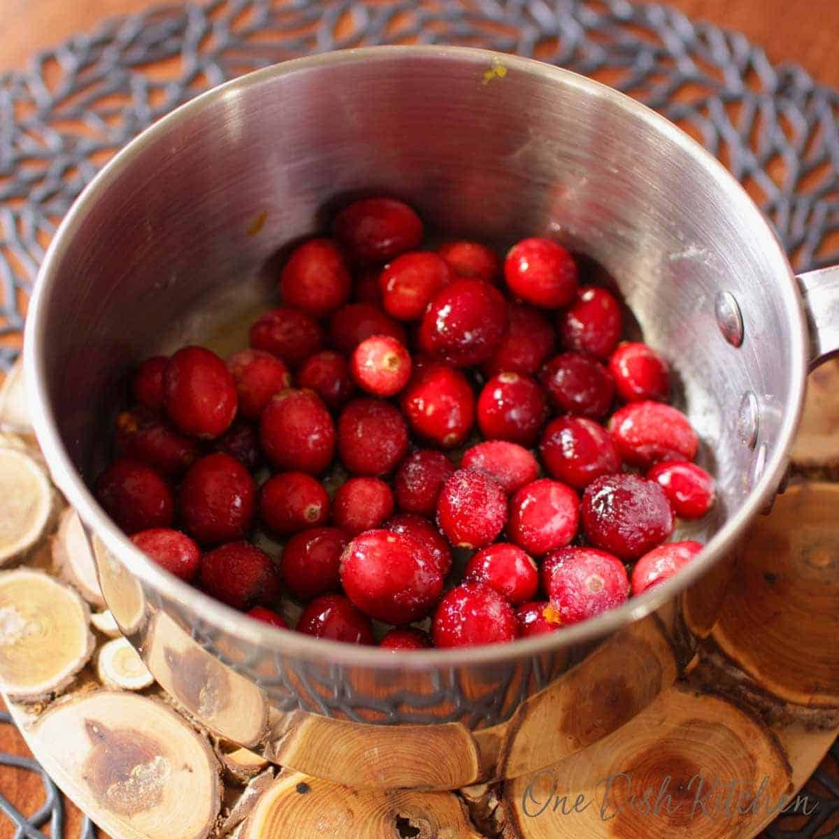 Cranberries and sugar in a pot on a wooden trivet
