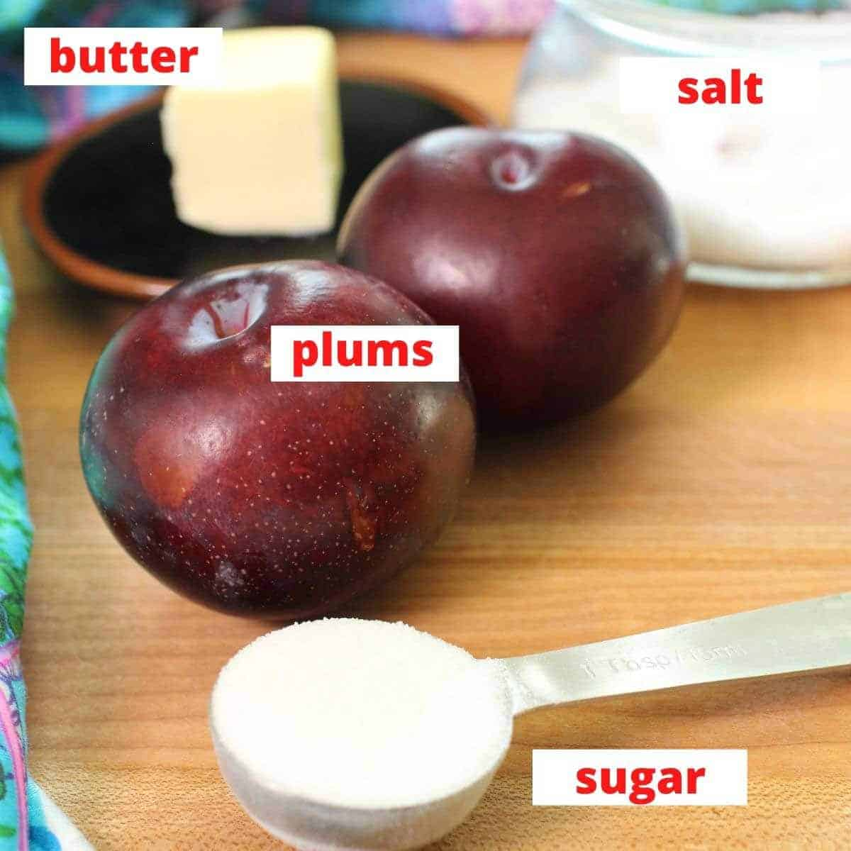the ingredients for caramelized plums on a brown table including 2 plums, sugar, and butter.