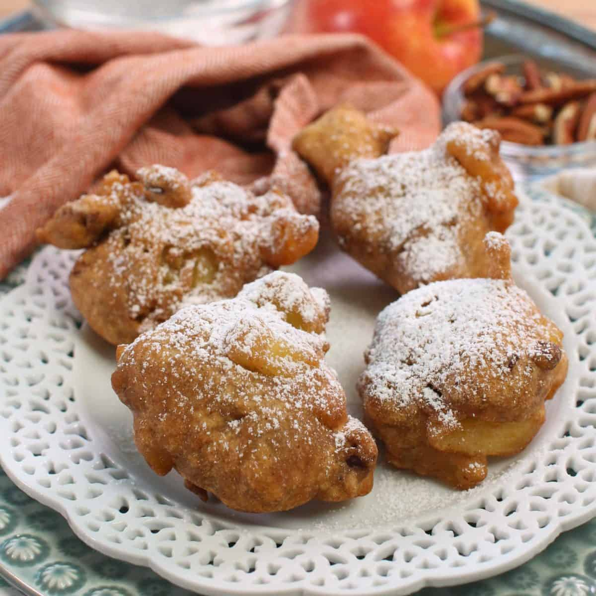 a close up of four apple fritters on a silver tray.