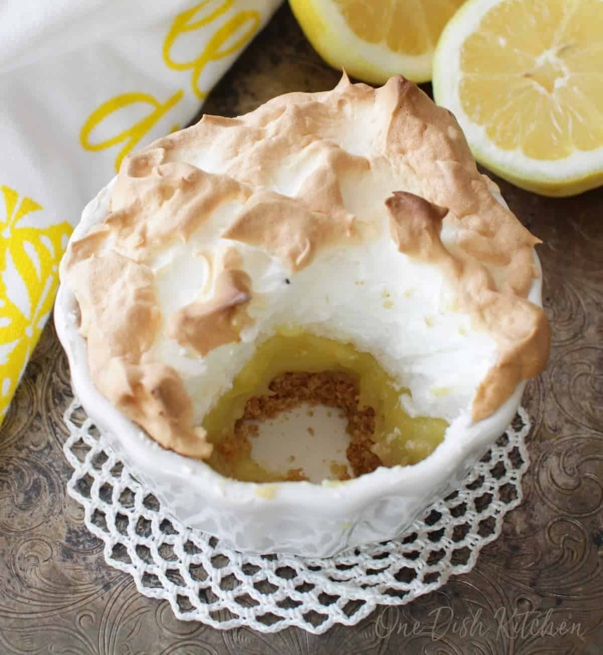 A small lemon meringue pie with a spoonful missing, showing the crust, filling and meringue in layers on a metal tray with two lemon halves