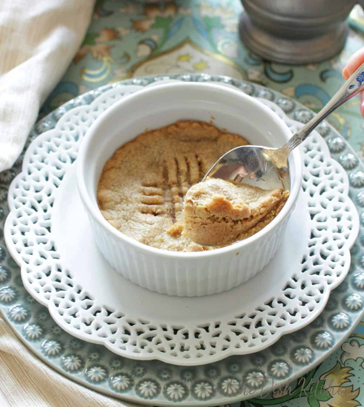 scooping out a spoonful of a cookie from a ramekin.