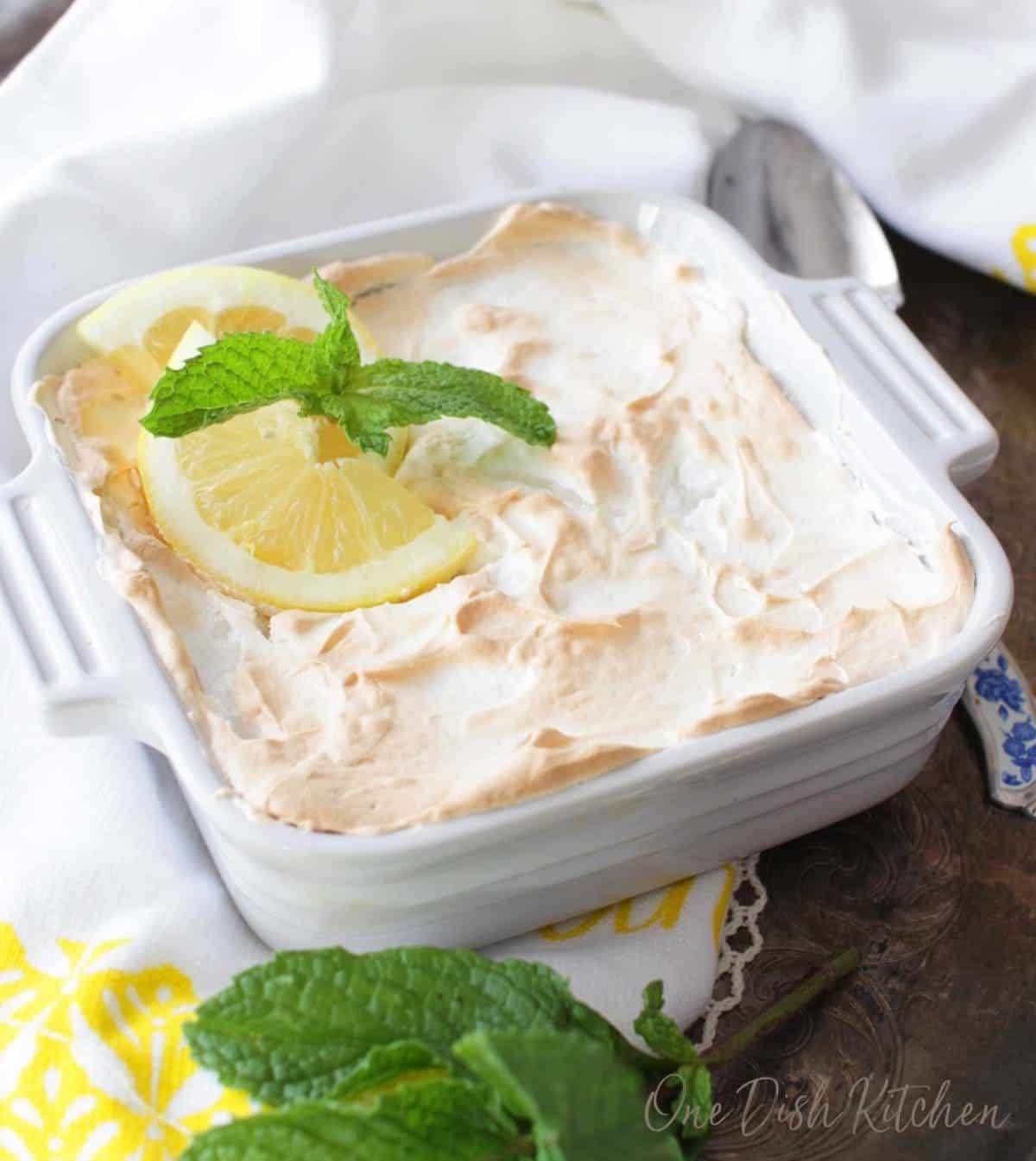 A mini lemon pie garnished with lemon slices and a sprig of fresh mint on a tray next to a yellow and white dish towel.