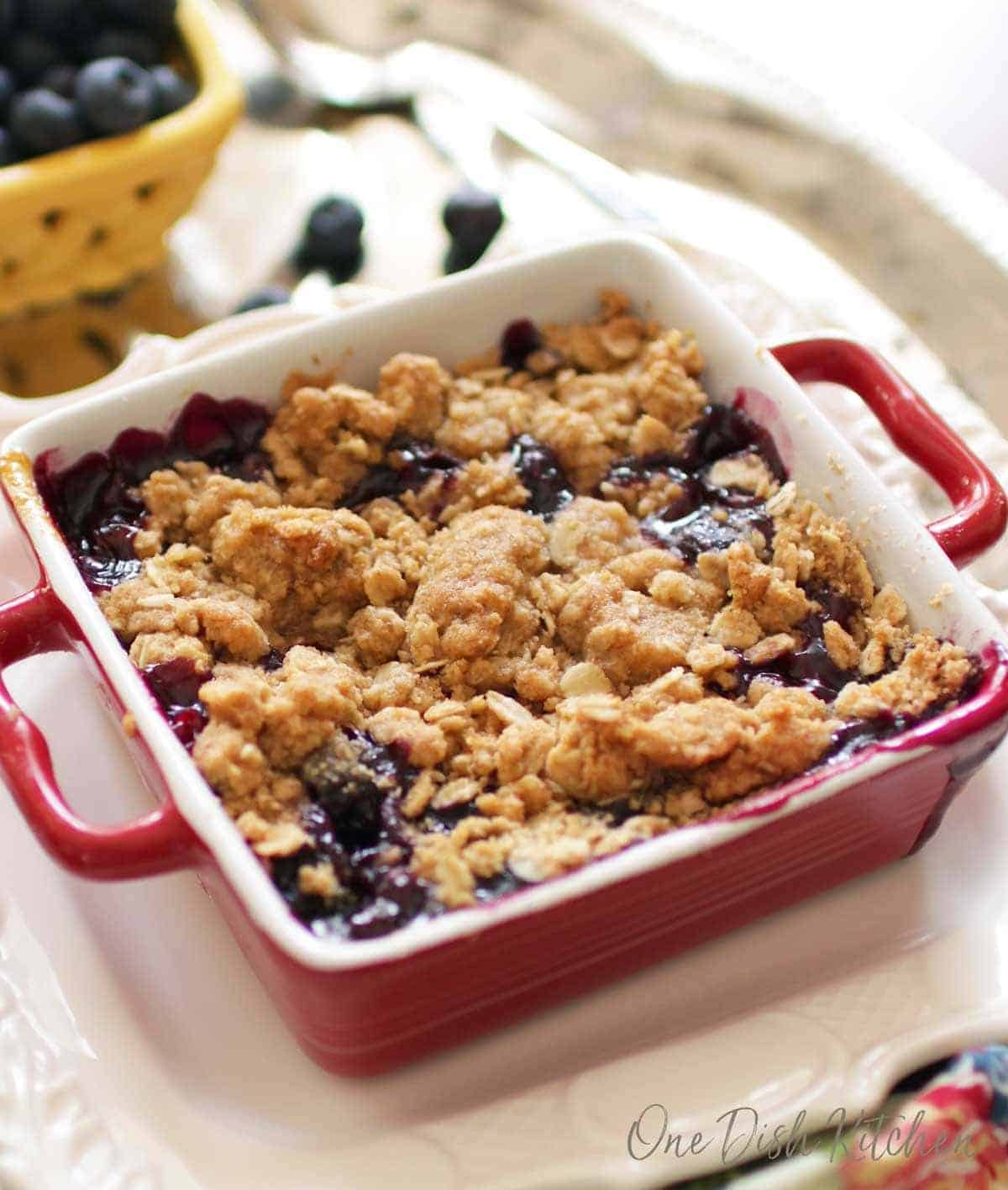 Blueberry crumble in a small red baking dish topped with baked oat topping