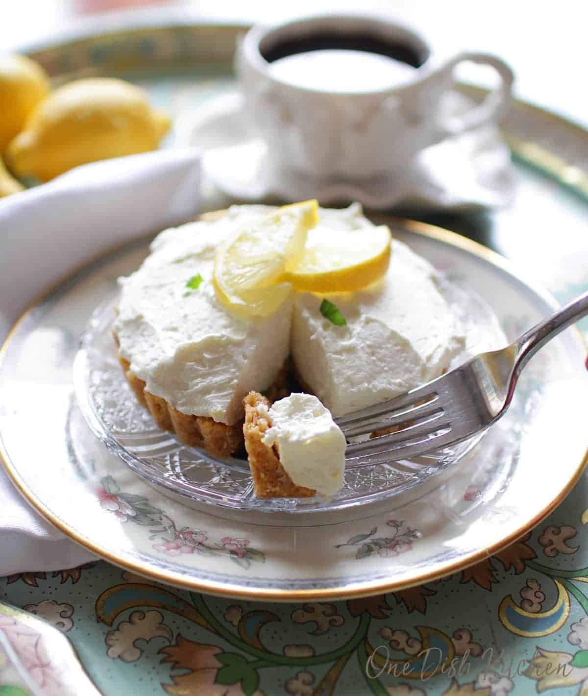 Forkful of lemon cheesecake mousse on a glass plate with whole lemons and a mug of coffee on a metal tray