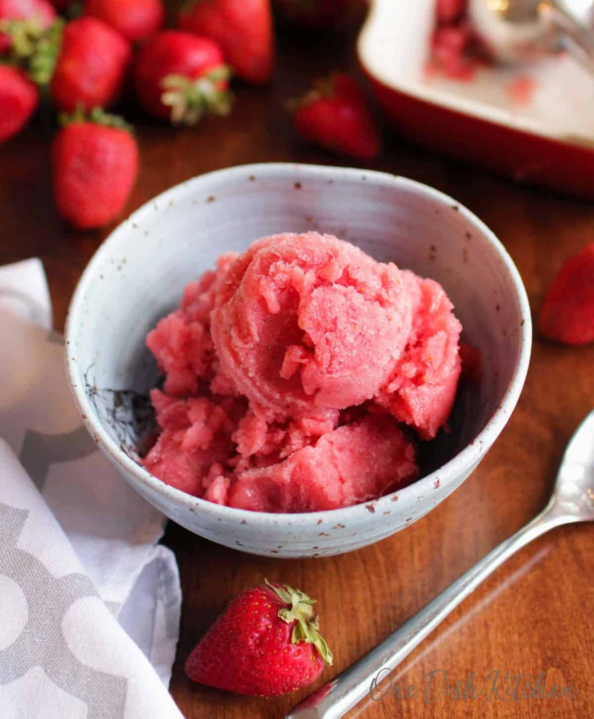 an overhead view of a bowl of strawberry sorbet next to strawberries scattered around a table.